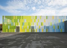 Sports hall in Lelystad, the Netherlands, by Slangen + Koenis Architects coloured in fluorescent shades of green, yellow and blue.