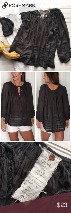 """Free People ONE Gauze Tunic Free People ONE Gauze Tunic   size XS/S; viscose . Charcoal grey tunic with deep v-notch and tie at neck   loose bell sleeves with elastic gather at wrist   pleat details on sleeves & hem   lightweight & flowy; slightly sheer   fit is oversized - would work for a M or L   hand wash cold . EUC, smoke-free home . 23"""" UA to UA 24.5"""" length Free People Tops"""