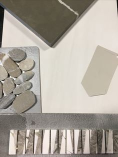 This pretty pick of the week has us swooning! The glossy white field tile allows the small (but stunning) marble deco band to really stand out. We selected a darker counter top to pull the deco colors together and provide contrast. Of course, we can't forget about the shower floor...so why not add the natural pebbles in with the mix!