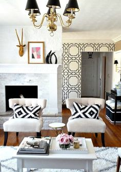 Modern Global style meets glam in this surprising living room design. A glamorous living room with global accessories on the fireplace mantle, patterned pillows and rug. Love the black and white patterned wallpaper in the background - Unique Living Room Ideas & Decor