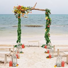 A driftwood arbor is adorned with fresh tropical flowers and greenery for summery, seaside nuptials.