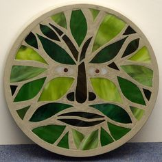 This concrete stepping stone is decorated with a stained glass mosaic featuring a Green Man design. Each circular stone is ( just under ) across and about ( just over inches ) thick. It should be bedded in the garden in the same way. Concrete Stepping Stones, Garden Stepping Stones, Concrete Art, Paving Stones, Garden Pavers, Mirror Mosaic, Mosaic Art, Mosaic Tiles, Mosaic Rocks