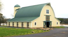Gothic arch barn with (curved) standing seam metal roof and shed roof wings. Wow!