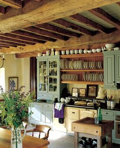 Vintage-inspired kitchen. Plate rack, butcher block, aqua cabinets.
