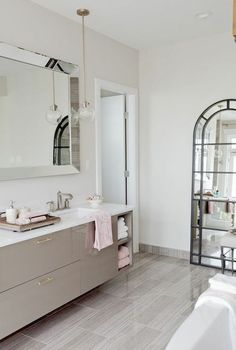 Contemporary bathroom with gray lacquered floating vanity accented with nickel pulls alongside white quartz counters which frame a rectangular porcelain sink paired with a modern faucet below a beveled vanity mirror lit by a glass sphere pendant hung from the ceiling.