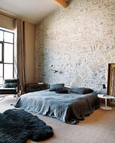I love this combination of modern stone walls, black sheepskin rug, dark furnishings & sultry bedding
