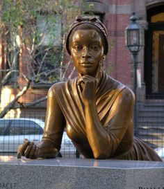 Wheatley, a slave in colonial Boston, was our first published African-American poet. Her pose is derived from the only extant image of her. She represents youth and Imagination.