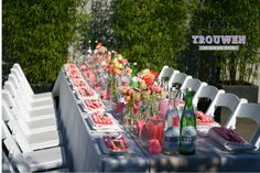Lange gedekte tafel in de tuin met bloem decoratie in de kleuren koraal, wit, neon en zacht roze.