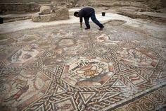 Un trabajador limpia un mosaico de 1.700 años antes de presentarlo al público el 16 de noviembre de ... - Proporcionado por AFP