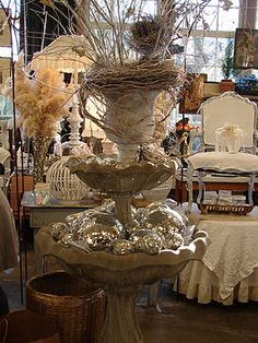 Sandra @ ribbonsandfavors.com Using stacked birdbaths and urns for displays.
