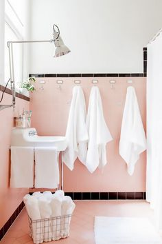 Bathroom with powdery-pink tile, a industrial light, and white accents