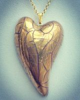 Gold heart with a vermeil chain. This heart has been made from porcelain by Claire Seneviratne.
