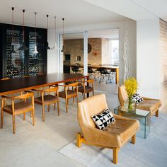 In the dining area, a custom wine rack doubles as a partition for the open plan. The adjacent door leads to an expansive enclosed terrace.