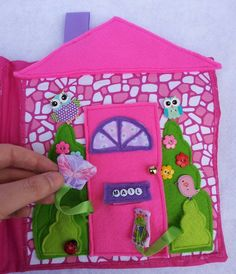 Dollhouse quiet book front cover. Has lots of decorative buttons. The door opens and a butterfly and a frog are in pockets behind the shrubs. The mail slot opens to reveal a letter with a personalized Christmas message for the little girl who this book is for. https://www.facebook.com/sparklesandstring
