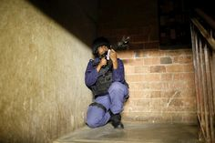 Johannesburg. April 2015. A policeman guards a stairwell during a raid on a hostel in Johannesburg's Alexandra township.  Photograph: Mike Hutchings/Reuters