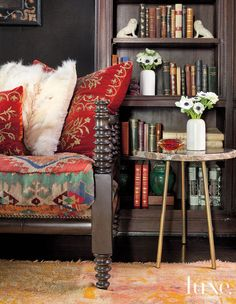 A kilim-covered French antique daybed from Brenda Antin is grouped with an onyx-topped side table from Blackman Cruz.