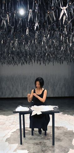 """The hovering mass of the downward-pointed scissors represent the distant fear and looming violence present in today's cultural climate. The sharp blades above the artist are put in contrast by the silent and simple act of mending. The dichotomous result of the instant fear superimposed with the calming effect of the sewing created a surreal atmosphere in the room."""