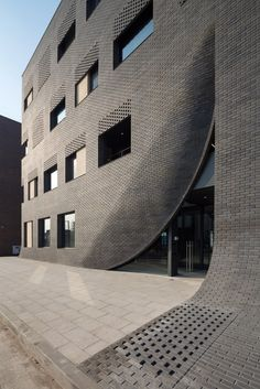 Entirely covered with black brick, the building has a twisted rectangular shape, and its entrance defined by the incised surface of the distorted structure makes it difficult to distinguish between the front and the back. In contrast to the torn entrance, 2m×2m large windows are installed as openings in order to enhance the sense of openness on the lower floors. To block out the excessive light flowing into the upper floors, the architect designed lintels to be closed gradually rather than…