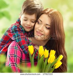Son hugging happy mother with flowers. Mother`s day concept. Family holiday