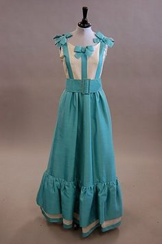 A Jean Patou Paris turquoise and ivory slubbed silk dress, late 1960s, labelled and numbered 86453, the bodice trimmed with bows to front and back and shoulders, deep flounced hem, broad belt. Front