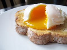 A single poached egg on artisan hand sliced toasted bread. The egg is split to reveal a runny yolk. ... - Jody Louie took this picture via Getty Images