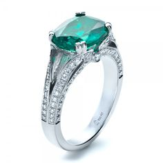 A large Chatham emerald mounted in a custom split shank and accented by rows of bright-cut-set diamonds.