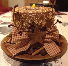 "Toilet Paper candle made by Jenifer Bryant Wring. She says to: "" spray paint a big roll of tp at least 3 coats, any color. Then brush on Elmer's glue and roll it in a mixture of oats, cinnamon and coffee...let dry and decorate it..I brushed the plate and star with glue and and dipped in coffee and cinnamon."""