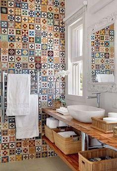 Neste lavabo, os coloridos ladrilhos foram combinados com cestos de vime, madeira e detalhes em branco.