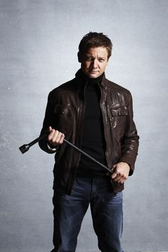 Jeremy Wearing Black Turtleneck, Brown Leather Jacket and Blue Jeans and Holding a Tire Iron