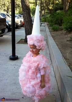 DIY Cotton Candy Costume.     Pink tshirt,  Pillow fill, Adhesive spray, Pink paint (for silk flowers),   Clown wig (with hair cut off and replaced with pillow fill),  light Poster board for cone,  Elastic to hold cone on head,   Pink polka dot knee highs, Blush and glitter for face + a cute kid! too cute!  @Sue Ledezma, this is too funny@