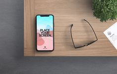 Freebie iPhone X in Desk 2 mockup PSD file with 2 smart objects editable screen of iphone x and the paper at the right, customizable ambient lights and reflections on the screen of the iphone x. You can use this mockup to show your work or any project you might have.