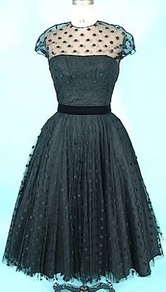 """1950's cocktail party dress with five layers of dotted Swiss, netting, acetate, and two  crinoline layers. Trimmed in black velvet around waist, cap sleeves of dotted Swiss over the """"Audrey"""" bodice. Designed by Karen Stark for Harvey Berin."""