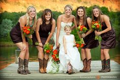 We love all the different colors in this photo: the purple bridesmaids dresses with the brown cowboy boots, and the orange bouquets. All so beautiful! #westernwedding #countrywedding