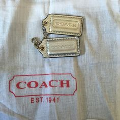 Authentic 2 silver & gold Coach key fobs There are 2 silver (1 is a brighter silver than the other) with gold hardware made out of leather Coach Key fobs. Come in dust cover. Coach Accessories