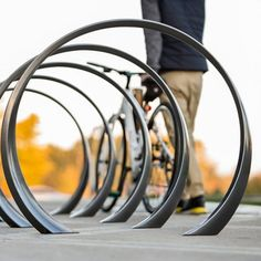 The Loop bike rack is a simple, sweeping circle with a twist. Both functional and sculptural, cyclists can loop and lock one or two bikes around its shape-shifting cast aluminum ribbon frame.