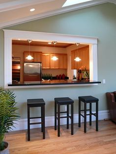 A simple pass-through adds a functional dimension and architectural interest to what otherwise would have been a big, blank wall, and enhances seating space to boot. These peekaboo openings, originally designed to provide a way to serve food from the kitchen while concealing any cooking mess, are as important for decorative appeal as they are for functional purposes.: