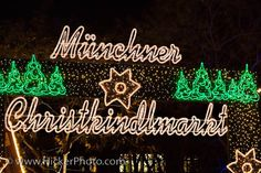 "Muenchner Christkindlmarkt Sign: A bright green and white sign saying ""Muenchner Christkindlmarkt"" marks the entrance to the Munich Christmas Markets in the city of Munich, Germany. The entrance to the annual christmas markets in downtown Munich is marked by a bright sign saying ""Muenchner Christkindlmarkt"". This sign is hung up each year and shows that the Muenchner Christkindlmarkt is open for business. Adorned with stars, green trees, and fairy lights the sign epitomizes christmas in downt..."