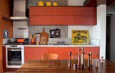 O apartamento de 80 m² não tem divisões entre a sala e a cozinha. A mesa de jantar fica logo na frente da bancada, com armários cor-de-laranja. Projeto do arquiteto Gustavo Calazans