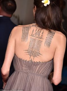 The 42-year-old Tomb Raider star was typically striking in a strapless grey grown, which displayed her sprawling back tattoo, as she posed on the carpet in the Big Apple - alongside her father, 78.