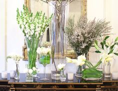 Varying heights of white flowers and all glass vases look great at a winter wedding reception #MarieeAmi #Weddings #Flowers