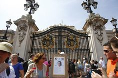 A bogus easel similar to the one that will be used to announce the royal baby's birth is placed outside the Palace as tourists mill around
