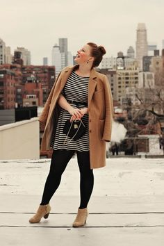 plus size camel coat, stripe dress, black tights. would be better w/ black shoes.
