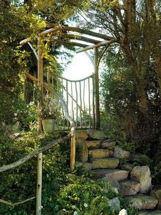 A charming gate and arbour fashioned from driftwood, weathered twigs and debarked cedar beckons visitors up the stone steps and into a sweeping cottage garden.