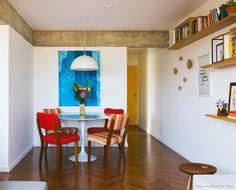 Sala de jantar mobiliada com mesa redonda saarinen e cadeira de madeira com…