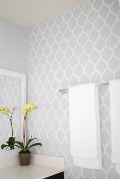 LOVE the simplicity of this guest bathroom, beautiful accent wall and pop of color with the potted flower.