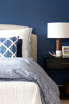 Navy walls, layered textiles. I'd love coloured walls with wood and white linens. Perfect.