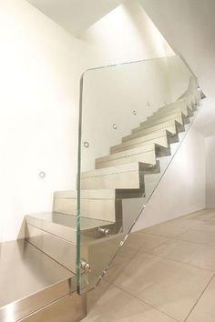 Closed cantilever staircase with stainless steel steps and risers, with ultra-clear structured glass banister.