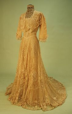 Edwardian fashion, 1900s women's fashion, Front View TRAINED HIGH NECK LACE on NET TEA GOWN, EARLY 20th C. Cream cotton net, the floral decorated bodice having lace neck insert and trim to three quarter sleeve, lappet front, back hook and eye closure, skirt embroidered with bands of clover alternating with ribbons, roses and lace insertion above scrolling border and deep hem flounce. Bust 32, waist 24, skirt length 45-57.