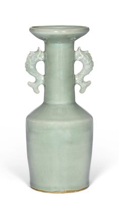 A 'Longquan' celadon mallet vase, Southern Song dynasty (1127–1279). Estimate 100,000 — 150,000 GBP. Photo: Sotheby's the cylindrical body rising from a low footrim to a canted shoulder sweeping up to a tall cylindrical neck, flanked on each side by a pair of dragon-fish handles, all below a wide everted dished rim with slightly upturned lip, covered overall with a sea-green glaze, draining to a paler tone at the edges, the unglazed hand-pared footrim of a buff colour; 30 cm, 11 3/4 in…