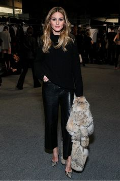 Olivia Palermo wears a black sweater, cropped leather pants, fur coat, and snakeskin pumps